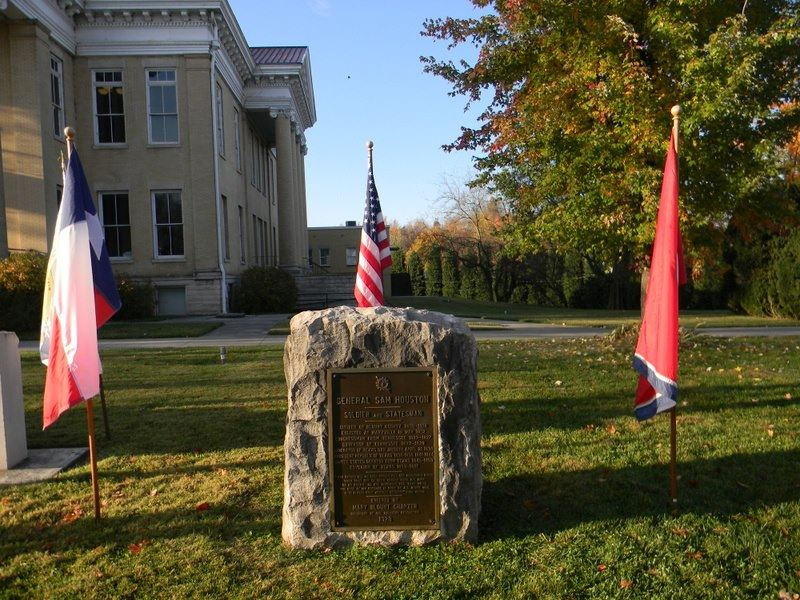 Image of the stone General Sam Houston Memorial with flags on perimeter